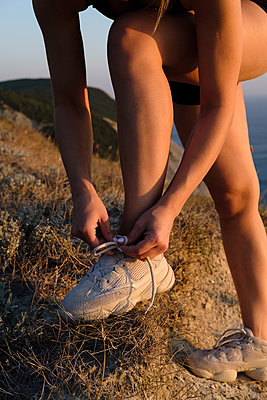 Athletic young woman is tying shoelaces on running shoes - p1363m2013479 by Valery Skurydin