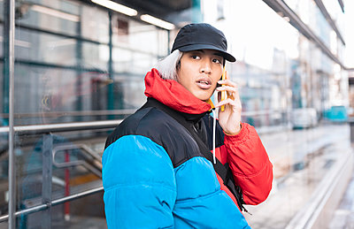 Young man talking on smart phone in city - p300m2252029 by Jose Carlos Ichiro