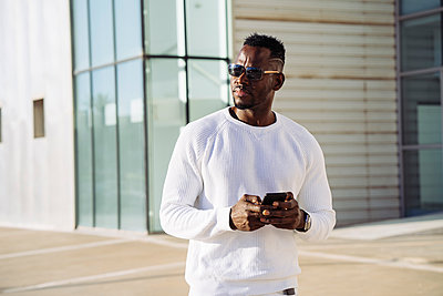 African man in sunglasses with smart phone against building - p300m2256963 by Manu Padilla Photo