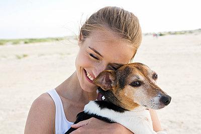 Junge Frau mit Hund am Strand - p341m1487835 von Mikesch
