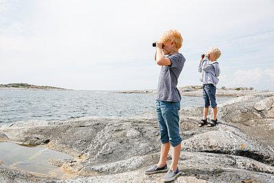 Sweden, Stockholm Archipelago, Sodermanland, Huvudskar, Two boys (6-7) (8-9) looking through binoculars on rocky seashore - p352m1349485 by Jenny Lagerqvist