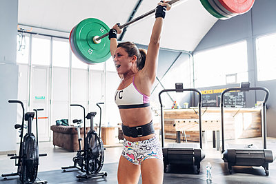 Woman weightlifting barbell in gym - p429m1569282 by Eugenio Marongiu