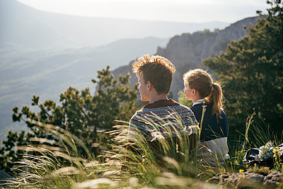 Caucasian couple sitting on hill admiring scenic view - p555m1219480 by Ivan Evgenyev