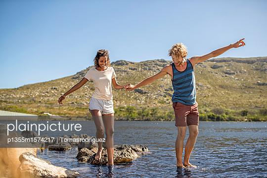 Junges Paar hat Spaß am Flussufer - p1355m1574217 von Tomasrodriguez