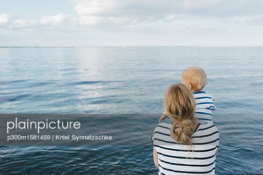 Germany, Timmendorfer Strand, mother holding his son - p300m1581459 von Kniel Synnatzschke