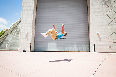 Young man somersaulting in front of a garage door.  - p1100m1038921 by Mint Images
