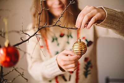 Midsection of woman hanging bauble on twig during Christmas at home - p1166m1547028 by Cavan Images