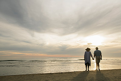 Back view of senior couple standing hand in hand on the beach watching sunset, Liepaja, Latvia - p300m2118483 by Hernandez and Sorokina