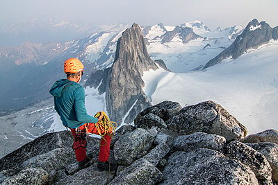 Mountain climber looking down at view from Bugaboo Spire, Bugaboo Mountains, British Columbia, Canada - p343m1554848 by Suzanne Stroeer