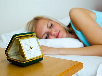 Girl sleeping next to alarm clock - p4266191f by Tuomas Marttila