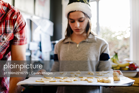Girl wearing santa hat holding tray with sugar cookies dough over Parchment paper. - p1166m2216779 by Cavan Images
