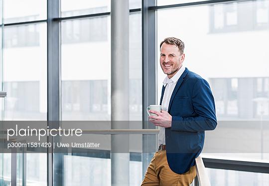 Portrait of smiling businessman having a coffee break - p300m1581420 von Uwe Umstätter