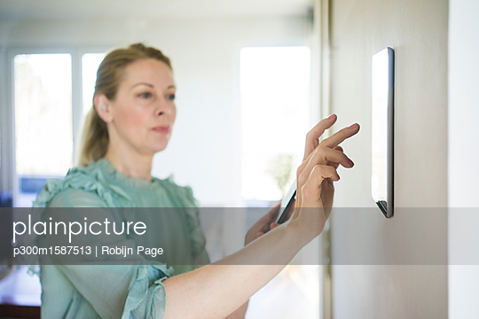 Woman adjusting digital tablet mounted on wall with smartphone - p300m1587513 von Robijn Page