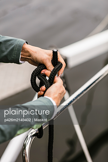 Cropped hands of senior female instructor tying rope on yacht's railing - p426m2149402 by Maskot