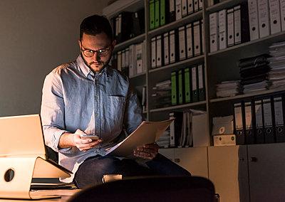 Businessman working late in office - p300m1581154 von Uwe Umstätter
