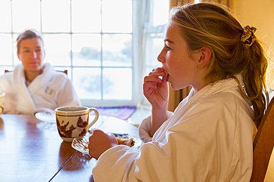 Caucasian girl eating breakfast in bathrobe - p555m1522794 by Marc Romanelli