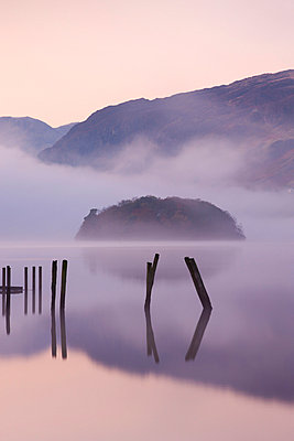 Old wooden jetty and St. Herbert's Island on Derwent Water at dawn on a misty autumn morning, Lake District National Park, Cumbria, England, United Kingdom, Europe - p8713042 by Adam Burton