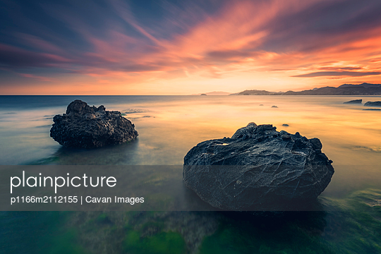 Scenic view of rock formations in sea against cloudy sky during sunset - p1166m2112155 by Cavan Images