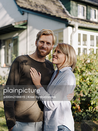 Portrait of smiling couple standing in front of their home - p300m2166615 by Kniel Synnatzschke
