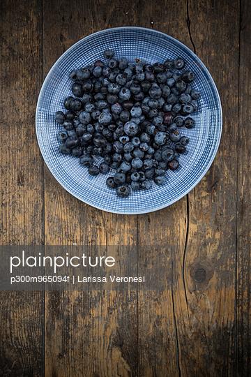 Dish of blueberries on wood - p300m965094f by Larissa Veronesi