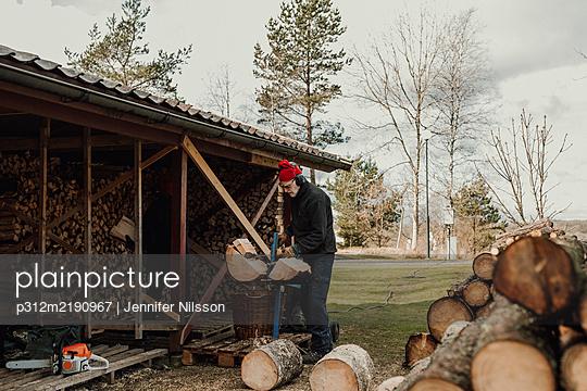 Senior man chopping wood - p312m2190967 by Jennifer Nilsson