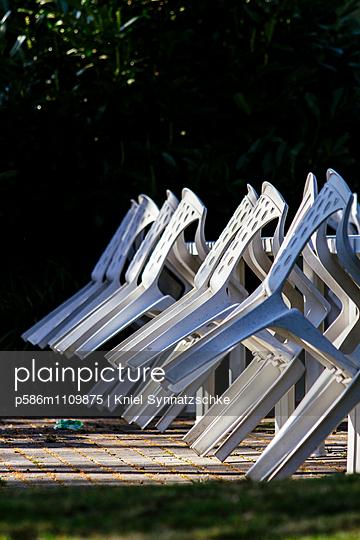 Weiße Plastikstühle in der Nebensaison - p586m1109875 von Kniel Synnatzschke