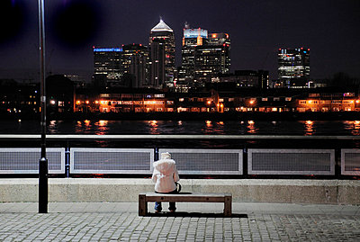 Woman sitting on a bench overlooking Canary Wharf at night - p1072m829394 by Neville Mountford-Hoare