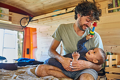 Father and son playing together in mobile home - p1146m2196064 by Stephanie Uhlenbrock