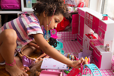 Mixed race little girl playing with toy kitchen sitting in her bedroom - p1166m2261917 by Cavan Images
