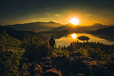 Person watching an early morning sunrise at Lake Bled - p1455m2043700 by Ingmar Wein