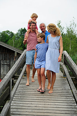 Happy family walking together on boardwalk in summer - p300m1549962 by Eyecatcher.pro