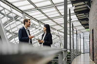 Smiling businessman and businesswoman with tablet talking in modern office building - p300m2156292 von Joseffson