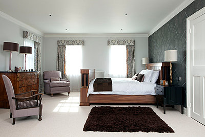 Wooden furniture and armchairs with feature wall and shagpile rug in Suffolk home  UK - p3493602 by Robert Sanderson