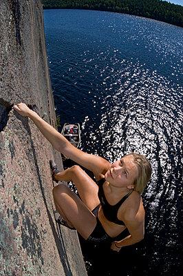 A woman rock climbing Sweden - p5751632f by Fredrik Schlyter