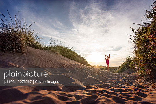 Joyful girl runs along sand dunes at beach at sunset in France - p1166m2078367 by Cavan Images