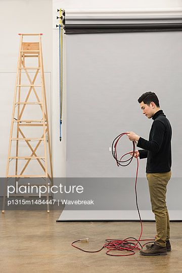 Full length of photographer rolling wire - p1315m1484447 by Wavebreak