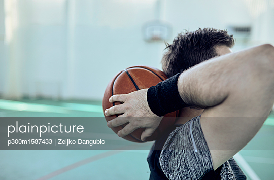 Man with basketball behind head, indoor - p300m1587433 von Zeljko Dangubic