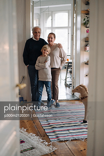 Portrait of happy grandparents with grandson at home - p300m2120331 by Gustafsson