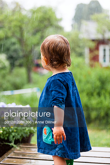 Toddler girl on patio in rain - p312m2086366 by Anne Dillner