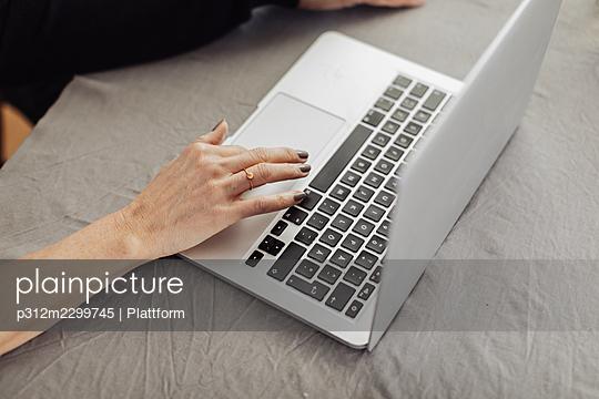 Woman's hand on laptop keyboard - p312m2299745 by Plattform