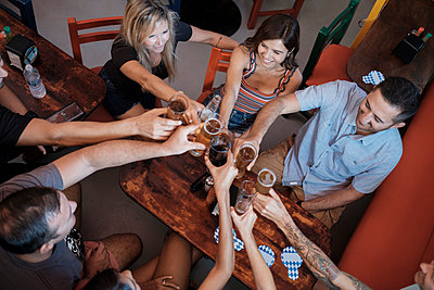 Friends socializing and clinking beer glasses in a bar - p300m2078569 by André Babiak