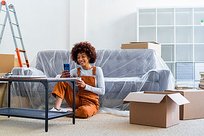 Smiling young woman using mobile phone while holding coffee cup in new apartment - p300m2251343 by Giorgio Fochesato