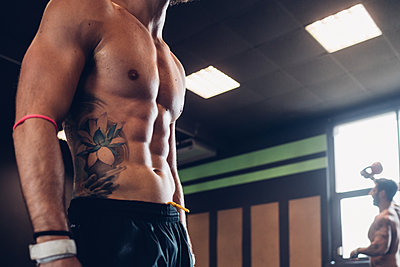 Young tattooed man training in gym, mid section side view - p429m2127510 by Eugenio Marongiu