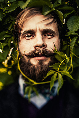 Vine curling around face of man with beard - p555m1305233 by Sophie Filippova
