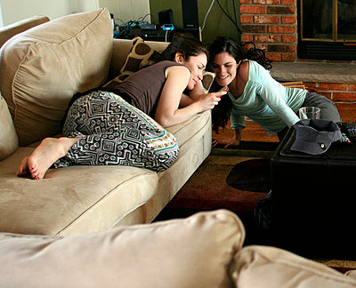 Women using cell phone in living room - p555m1409005 by Shestock