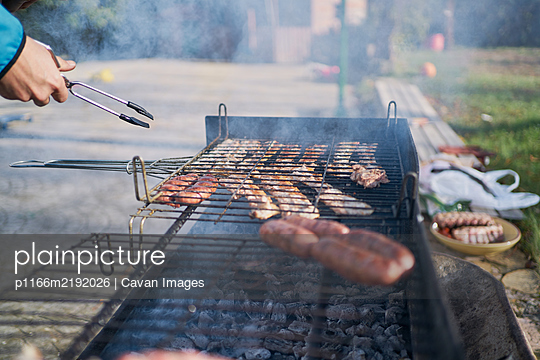 preparation of barbecue on bacon and sausage grill - p1166m2192026 by Cavan Images