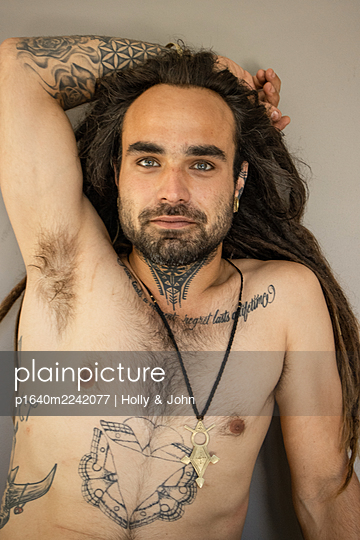 Young man with bare chest and lots of tattoos - p1640m2242077 by Holly & John