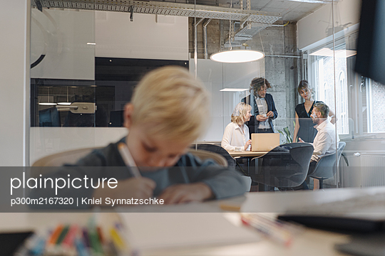 Boy painting in office with business team having a meeting - p300m2167320 by Kniel Synnatzschke