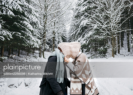 Romantic couple covering face with scarf while standing on snow in forest - p300m2256098 by Katharina Mikhrin
