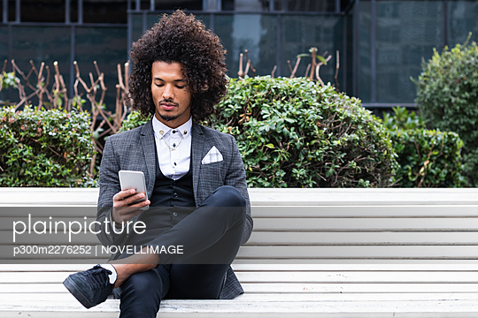 Handsome young businessman using mobile phone on bench - p300m2276252 by NOVELLIMAGE